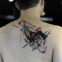 Modern style colored upper back tattoo of wolf head combined with lettering