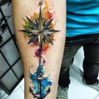 Modern traditional style colored forearm tattoo of compass and roped anchor