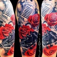 Modern traditional style colored shoulder tattoo of vintage microphone with roses and guitar