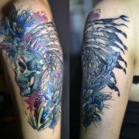 Multicolored upper arm tattoo of Indian skull with helmet and flowers by Joanna Swirska
