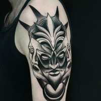 Mysterious blackwork style upper arm tattoo of demonic face by Michele Zingales