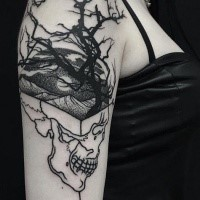 Mystical looking black ink shoulder tattoo of human skull with tree and mountains