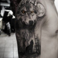 Mystical looking colored upper arm tattoo of wolf in forest with yellow eyes