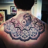 Mystical style colored owl tattoo on upper back stylized with sun