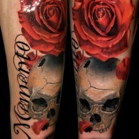 Natural colored big red rose tattoo on forearm with corrupted skull and lettering