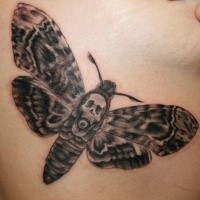 Natural looking black ink butterfly tattoo with skull