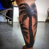 Natural looking black ink palm tree tattoo on leg