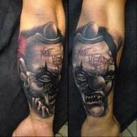 Natural looking colored 3D forearm tattoo of crazy monster clown with lettering