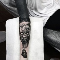 Natural looking very detailed forearm tattoo of zombie head combined with human heart