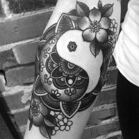 New school style black ink arm tattoo of Yin Yang symbol stylized with flowers