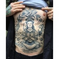 New school style black ink painted by Michael J Kelly chest and belly tattoo of Buddha with lettering