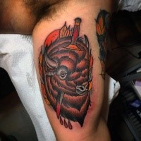 New school style colored biceps tattoo of bull with bloody knife