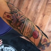 New school style colored forearm tattoo of Harry Potter movie letter