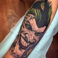 New school style colored forearm tattoo of evil Joker