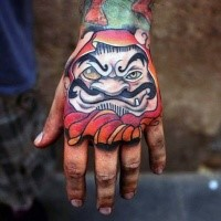 New school style colored hand tattoo of daruma doll head