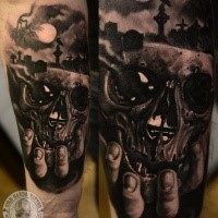 New school style colored tattoo of hand holding skull with cemetery