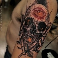 New school style colored upper arm tattoo of human skull with eye and leaves