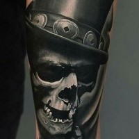 New school very realistic style forearm tattoo of human skull with cylinder
