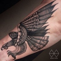 Nice looking black ink arm tattoo of big flying eagle