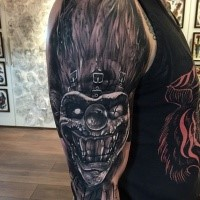 Nice looking colored arm tattoo of crazy monster clown face