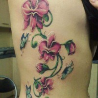 Nice pink orchids with butterflies tattoo on ribs