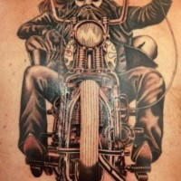 Old biker on a motorcycle tattoo on back