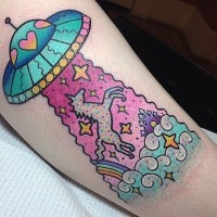 Old cartoon like colored leg tattoo with alien ship and unicorn with stars