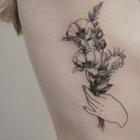 Old looking detailed side tattoo of hand holding flowers by Zihwa