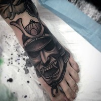 Old school black ink little samurai helmet tattoo on foot