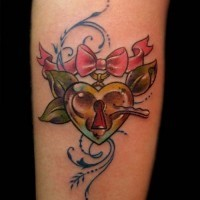Old school colored heart shaped lock tattoo on forearm stylized with pink bow