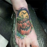 Old school colored little pumpkin tattoo on foot with bats and moon