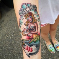 Old school colored mermaid and shark tattoo on forearm stylized with lettering