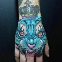 Old school colored mystical blue tiger tattoo on hand with little crown