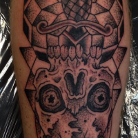 Old school style black ink leg tattoo of creepy skull with dagger