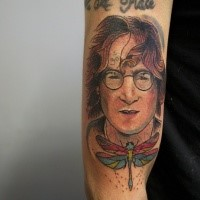 Old school style colored arm tattoo of Lennon face with dragonfly