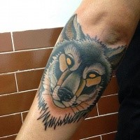 Old school style colored arm tattoo of wolf with yellow eyes