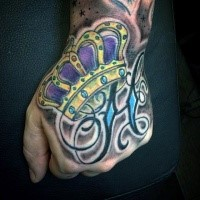 Old school style colored crown tattoo on hand with lettering