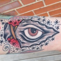 Old school style colored little arrow head tattoo on forearm stylized with eye and stars