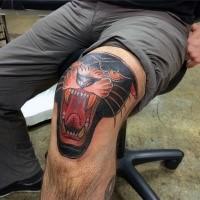 Oldschool Stil brüllender schwarzer Panther Kopf gefärbtes Knie Tattoo
