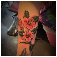 Old school style pale pink hibiscus flowers branch tattoo on forearm with Hawaiian motifs