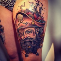 Old style painted colored pirate with ship tattoo on thigh