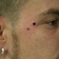 Tatuaje de estrella negra diminuta en la cara