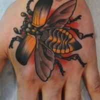 scarabeo volante arancione tatuaggio sulla mano