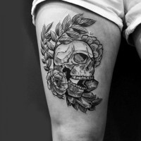 Original designed black and white skull tattoo on thigh stylized with flowers and feather