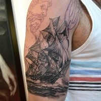 Original looking colored shoulder tattoo of sailing ship in waters