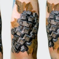 originale dipinto colorato tasti della tastiera con foglie tatuaggio su braccio