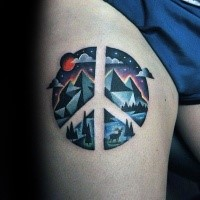 Pacific symbol shaped thigh tattoo stylized with mountains and night sky