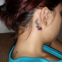 Pale of colored books stylized with flock of birds tiny tattoo on neck behind ear