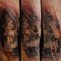 Photoshop style colored arm tattoo of alien skull with lettering