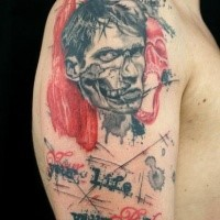 Photoshop style colored shoulder tattoo of human zombie with lettering